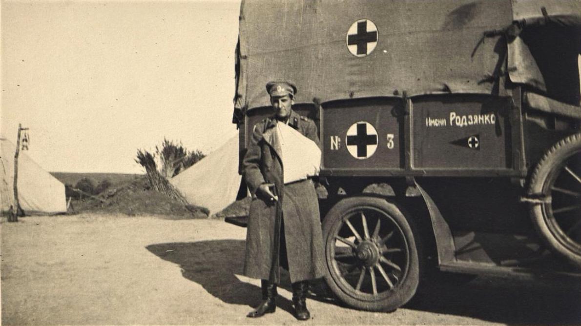 Офицер с рукой на перевязи у автомобиля Красного Креста. 1914-1916 гг.