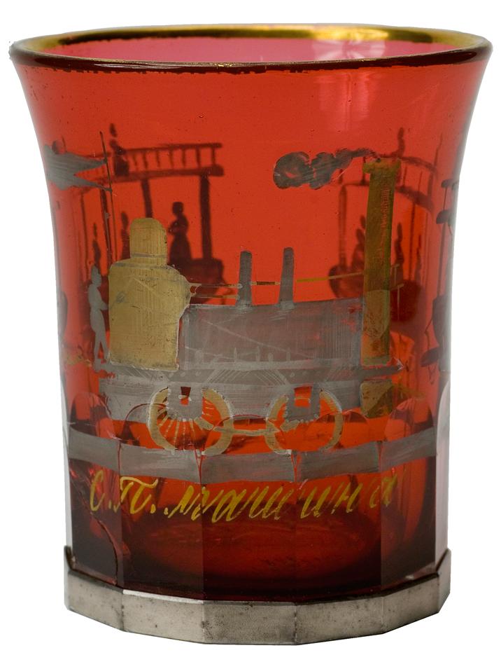 """Стакан с изображением паровоза и надписью: """"СП машина"""". Императорский стеклянный завод, 1837 год. Стекло """"золотой рубин""""; выдувание, гранение, роспись золотом и серебром."""
