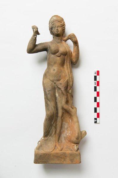 Терракотовая фигура Афродиты, стоящей с дельфином. IV в. до н. э. Пантикапей, некрополь. Таврическая губ., г. Керчь