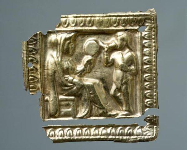 Бляшка с изображением женщины на табурете и стоящего с ритоном скифа. Около 350 г. до н. э.